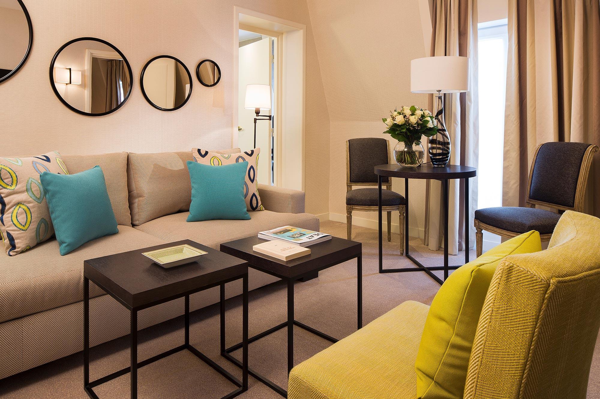Salon d'une suite avec canapé et fauteuil couleurs beige et jaune, détails déco et coussins bleu, tables basses avec livres et bouquet de fleurs