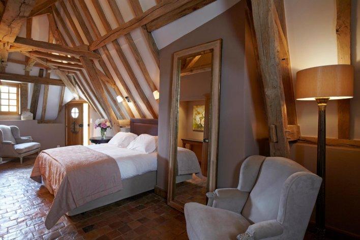 Chambre double avec poutres apparentes, décoration miroir et fauteuil beige