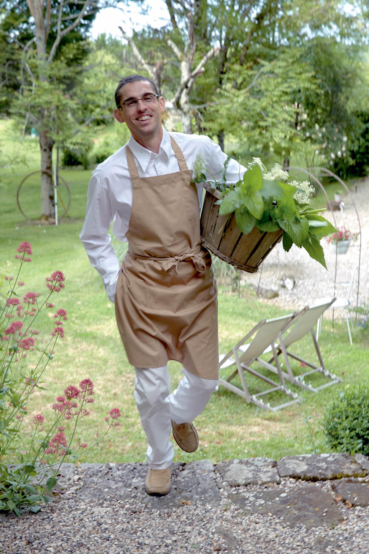 Chef en tablier beige et habits blanc revenant du jardin avec un panier d'herbe et de plantes