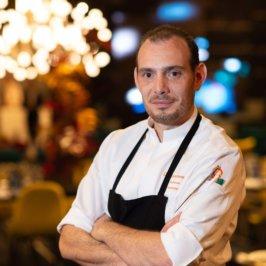 Chef en tablier noir et veste blanche logotée oméga orange des Collectionneurs