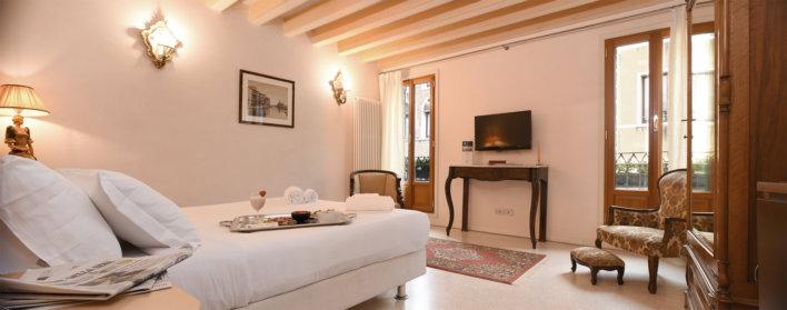 Chambre prise en photo en diagonal avec un lit double et un plateau de petit-déjeuner sur le lit