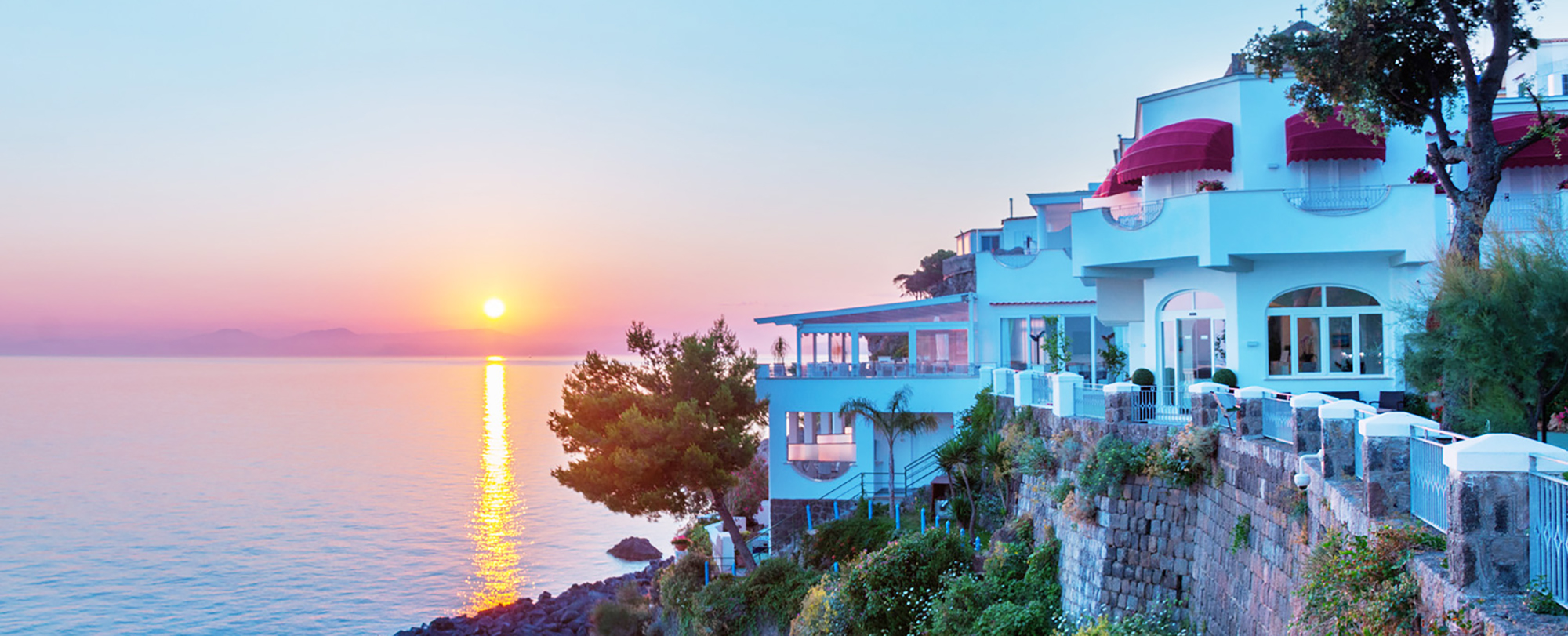 Photo pris en hauteur en haut d'une petite falaise où se trouve l'hôtel. On peut y voir un magnifique coucher de soleil et la mer