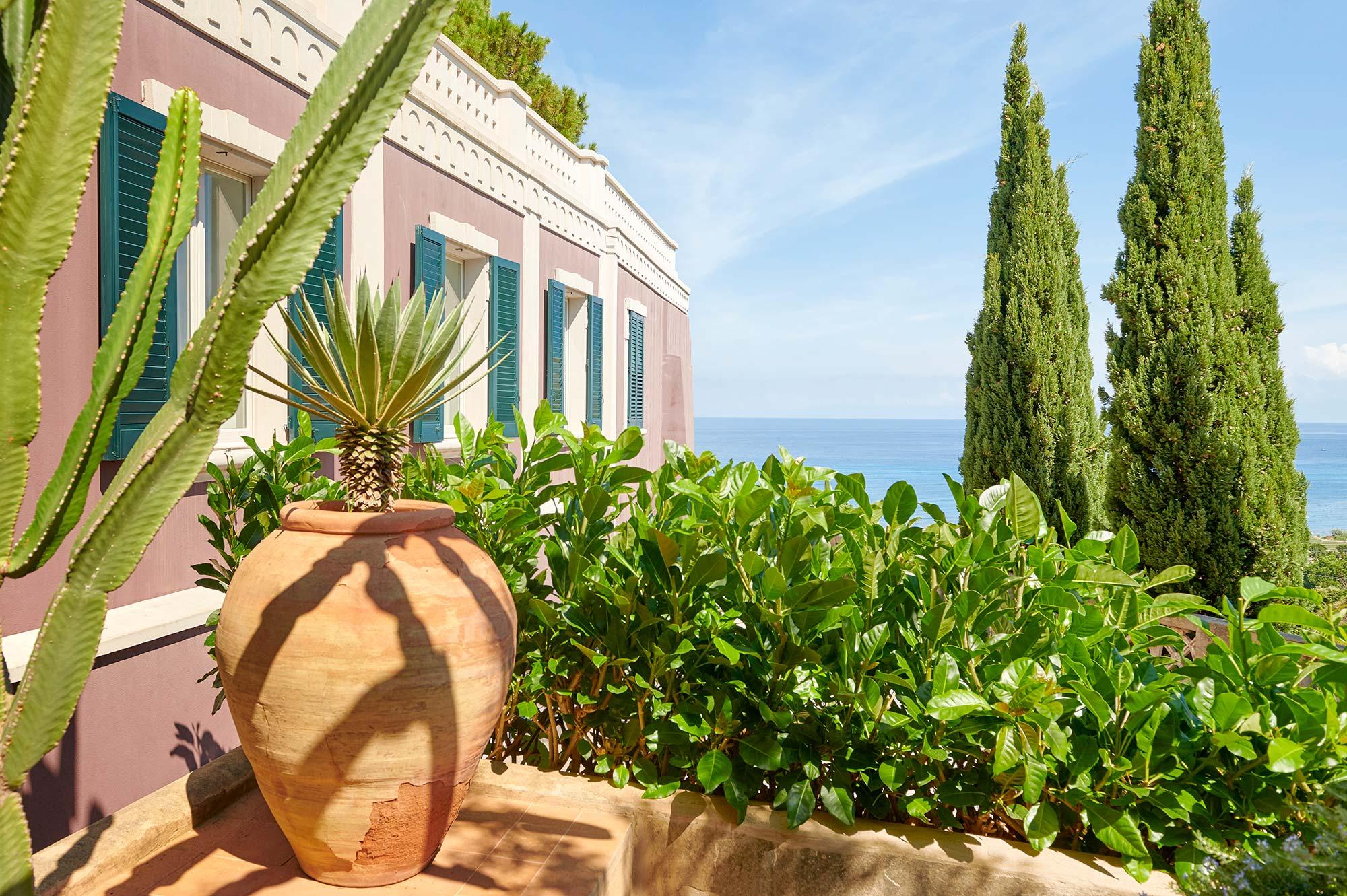 Photo de détail prise sur une terrasse avec une amphore en terre cuite, végétation verdoyante et maison typique du sud de l'Italie
