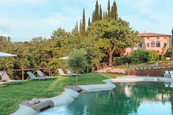 Vue sur une piscine bordée d'une étendue verte, forêt et bâtisse typique de toscane en arrière-plan