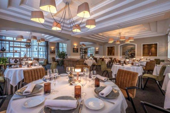 Salle de restaurant, lustre à 6 appliques, tables dressées dans les ton nappée blanc, vaisselle beige et blanche