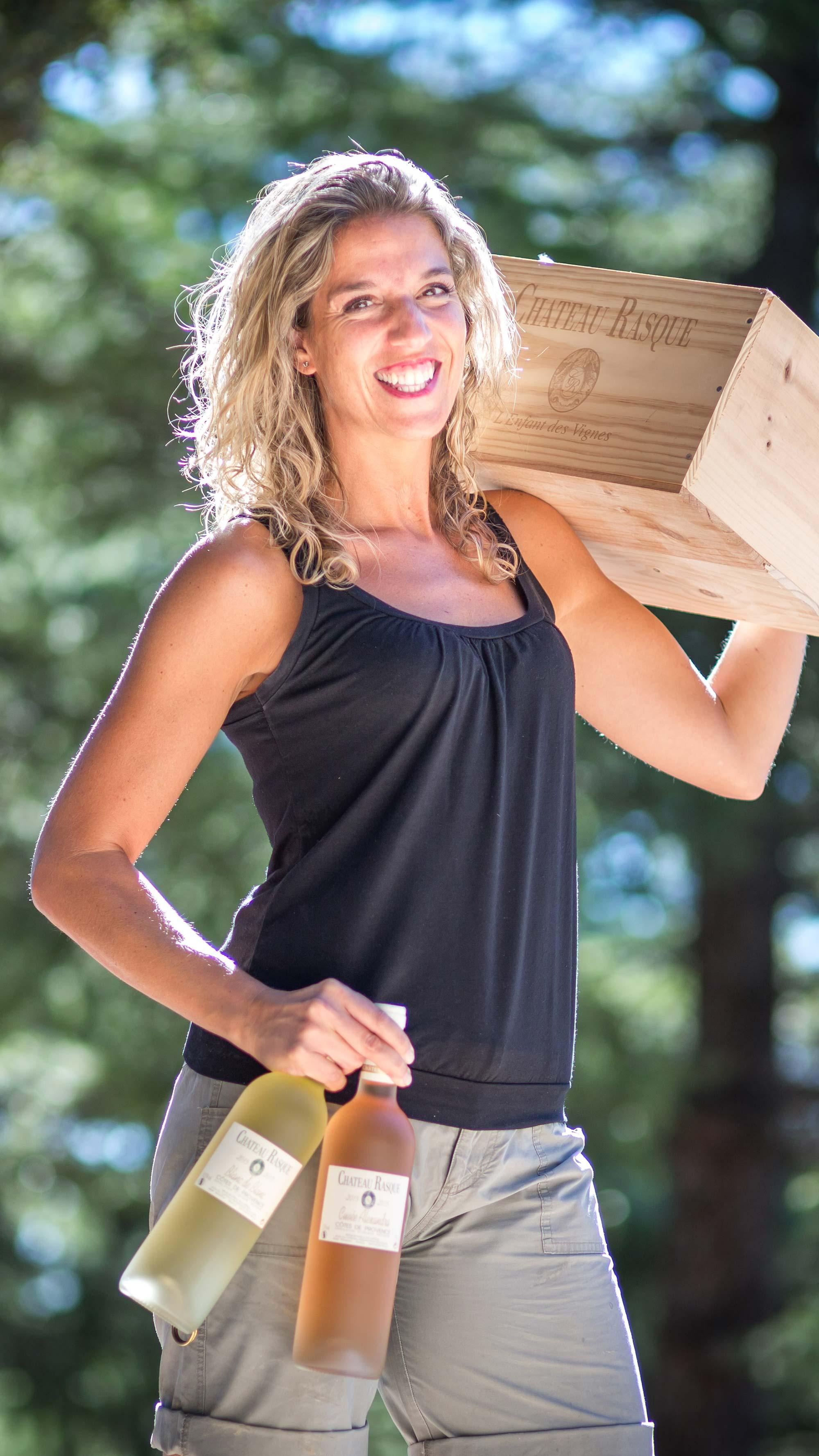 Femme tenant une caisse de vin sur l'épaule avec le bras gauche et deux bouteilles de vin (un blanc et un rosé) dans la main gauche