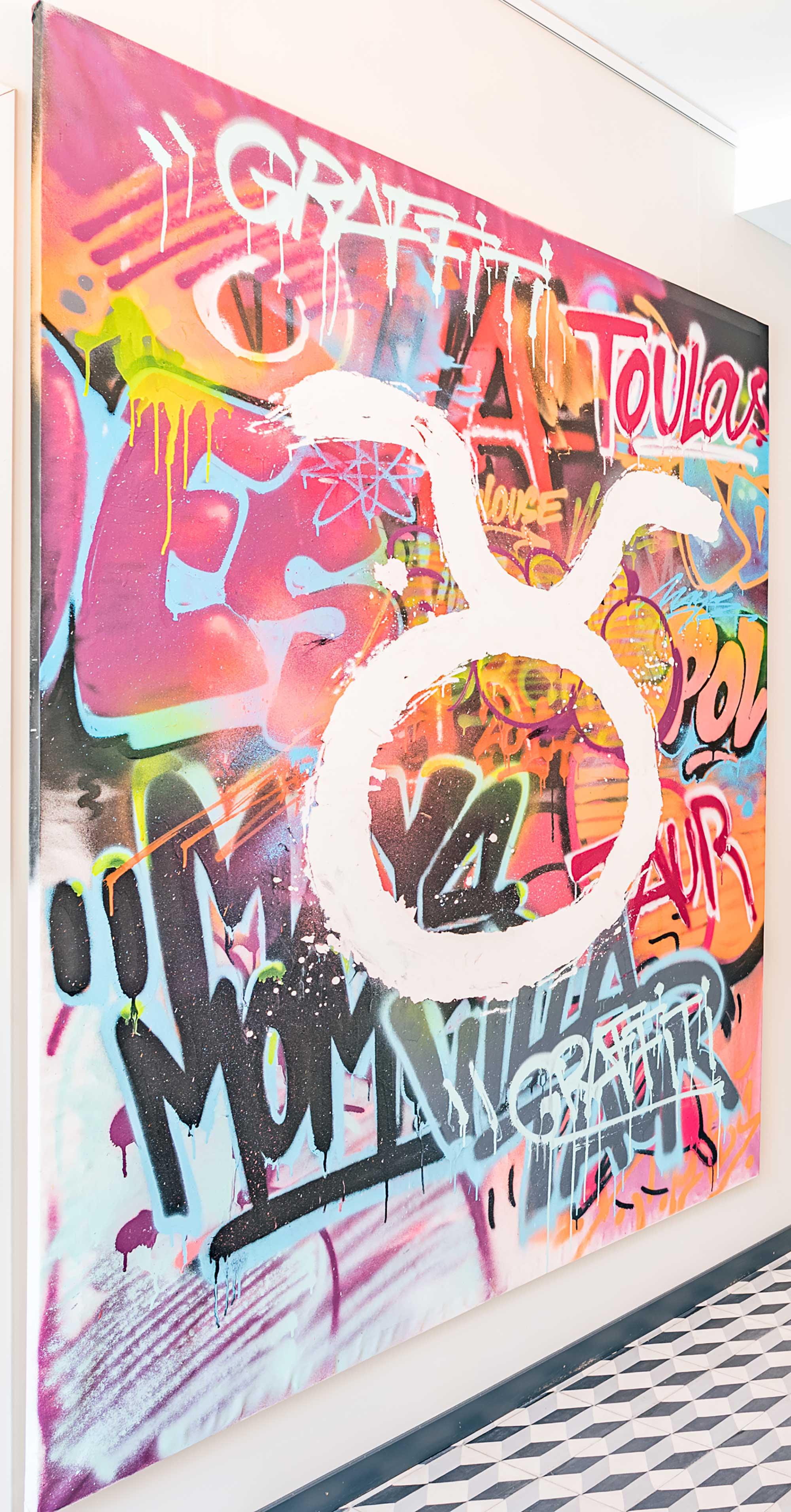 Toile peinte en graffiti, bombe de toutes les couleurs avec un logo qui blanc comme un oméga inversé