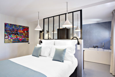 Chambre double avec tête de lit verrière donnant sur une salle de bain avec baignoire, une toile en peinture aérosol accroché sur le côté du lit
