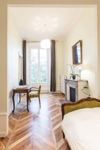 Chambre avec grande porte fenêtre, parquet en chevron et cheminée en marbre