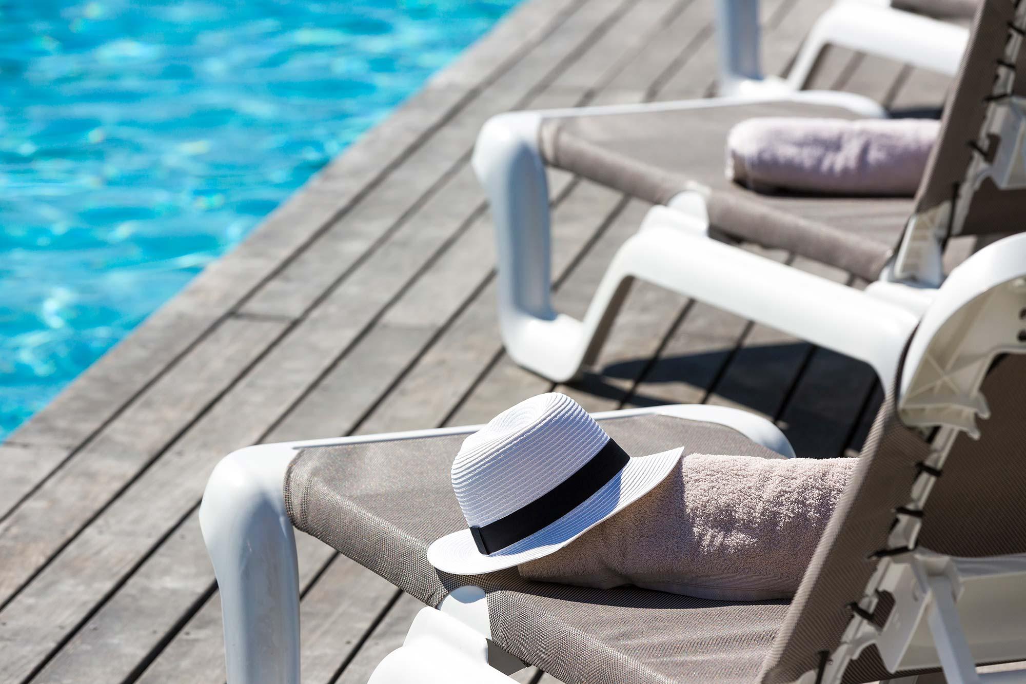 Détail de transat en bord de piscine avec canotier