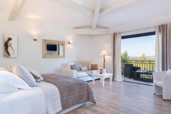Chambre parquet clair, lit double, canapé, poutres apparentes et balcon avec salon de jardin, décoration intérieure dans les ton blancs et beiges