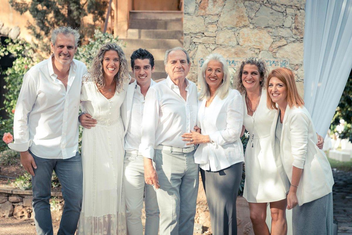 Photo de famille, hommes et femmes, en tenues blanche, bâtisse provençale en arrière-plan