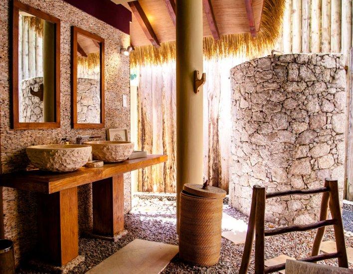 Salle de bain en matérieaux bruts : pierres, bois, galets et toit naturel