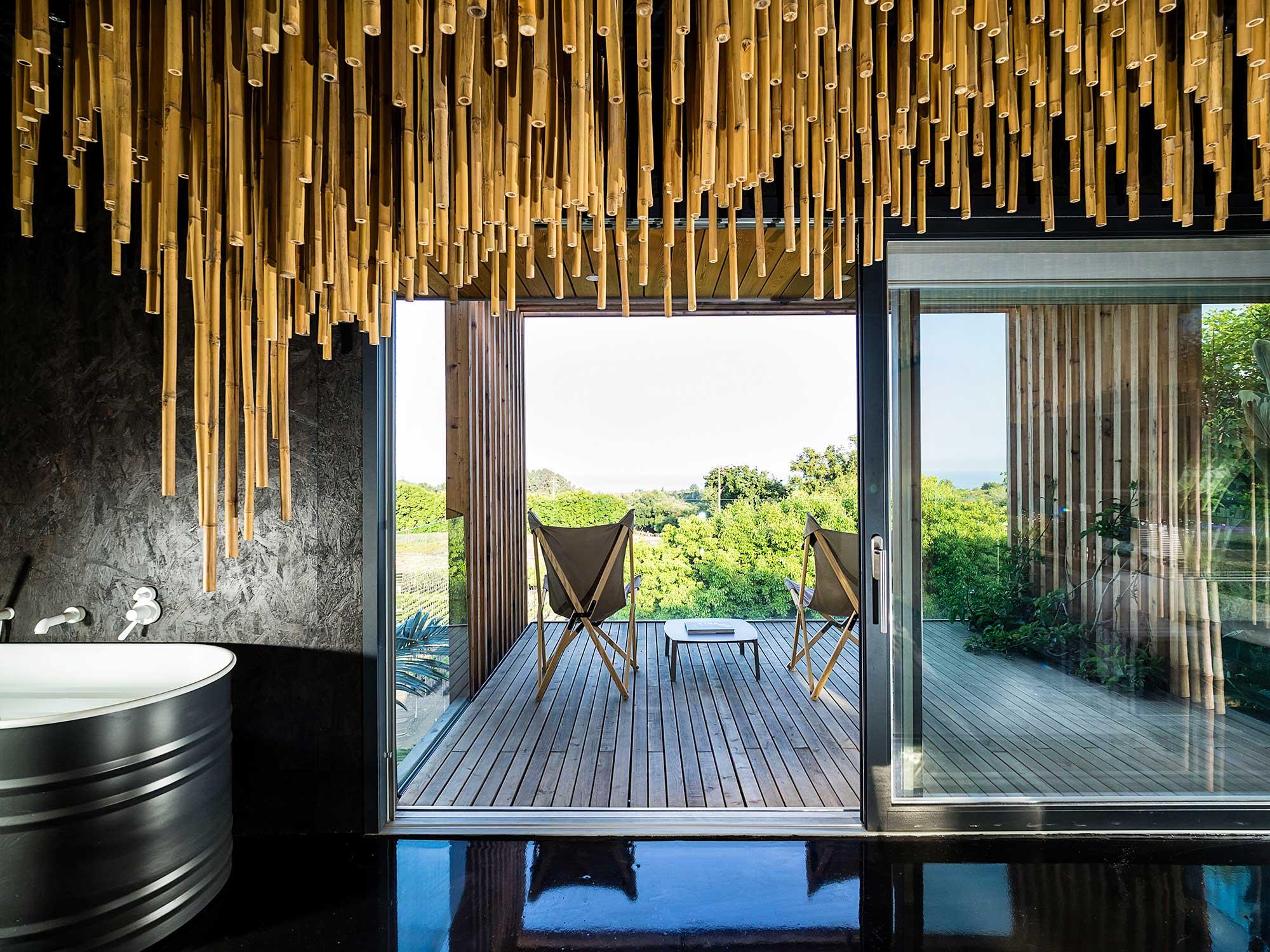 Baignoire dans salle de bain design avec mur noir en ardoise et bambou suspendu au dessus, vue sur terrasse privative et horizon verdoyant