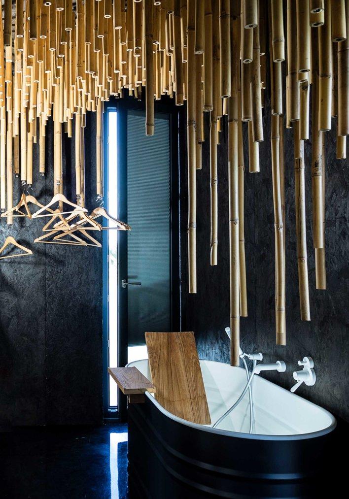 Baignoire dans salle de bain design avec mur noir en ardoise et bambou suspendu au dessus