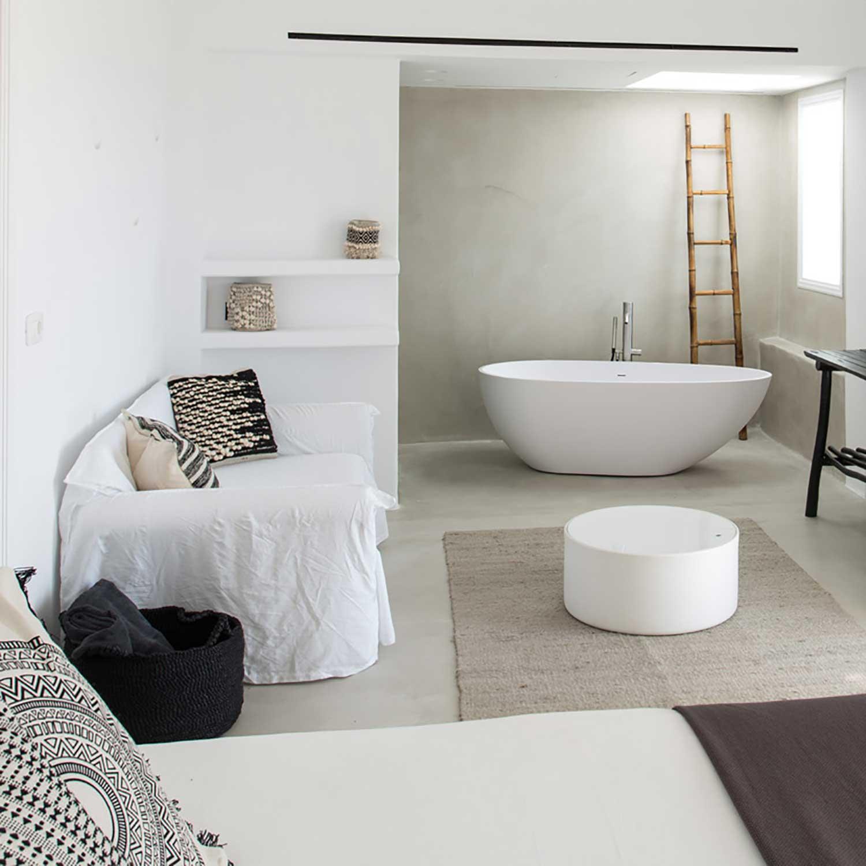Suite avec salle de bain ouverte, baignoire centrale, décoration matériaux naturels