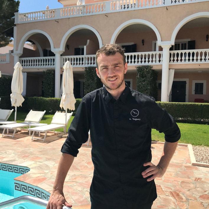 Chef en veste noir, arrière plan hôtel avec alcôves et piscine sur le côté gauche
