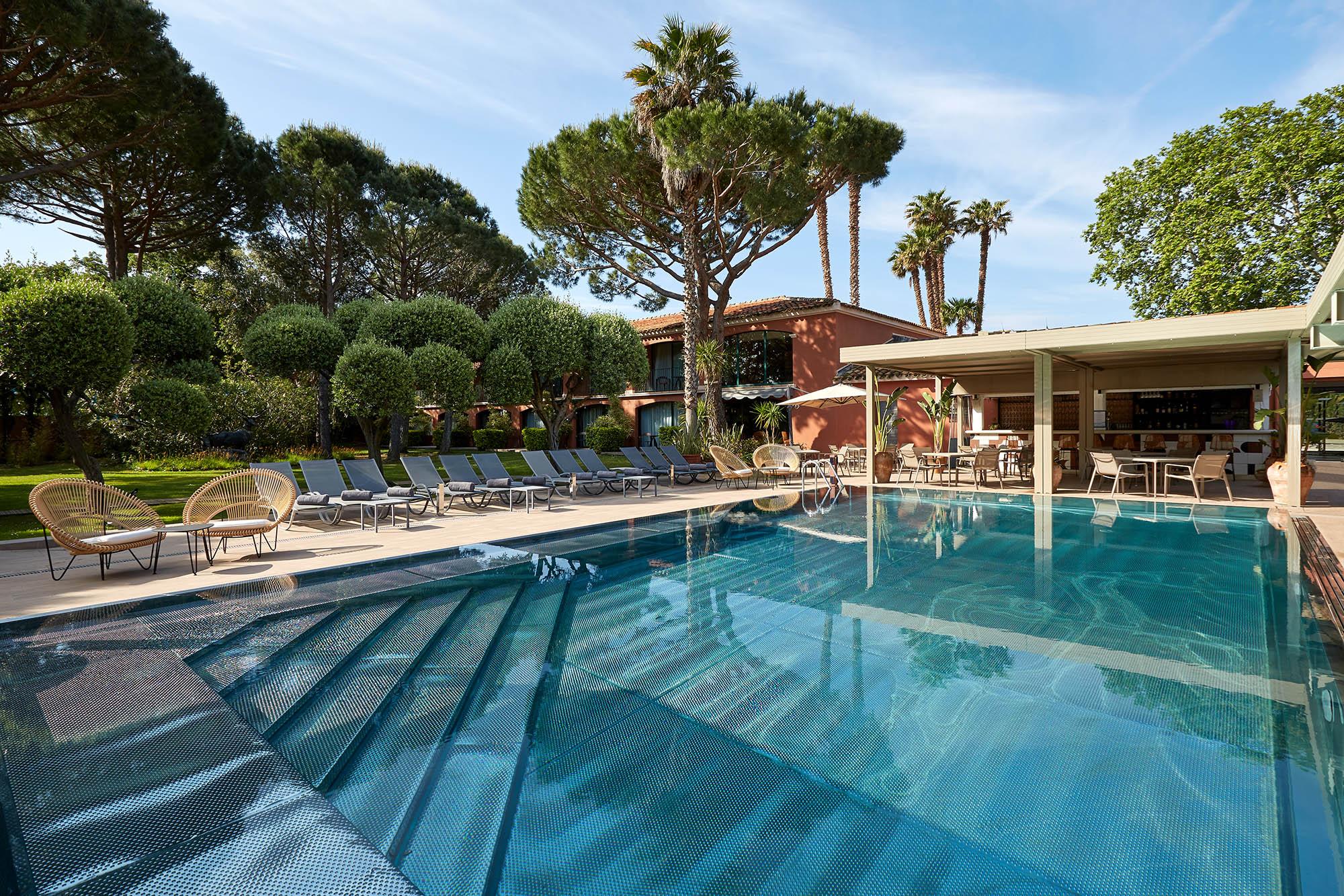 photo de la piscine extérieure prise en plein jour avec les transats au bord de la piscine