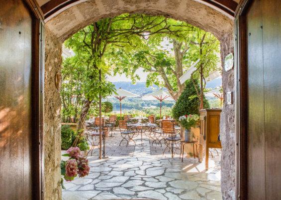 Portes en bois ouvertes donnant sur une terrasse arborée dans le sud de la France.