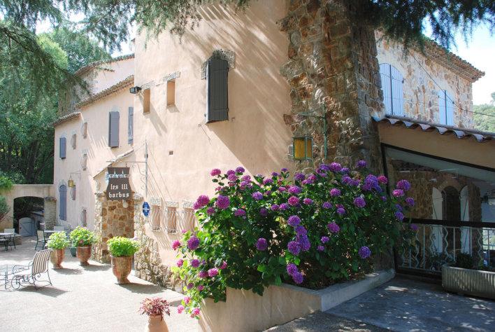 Photo de la façade prise de profil. On y voit des fleurs violettes au bord de la façades et quelques pots de fleurs à l'entrée et une chaise.