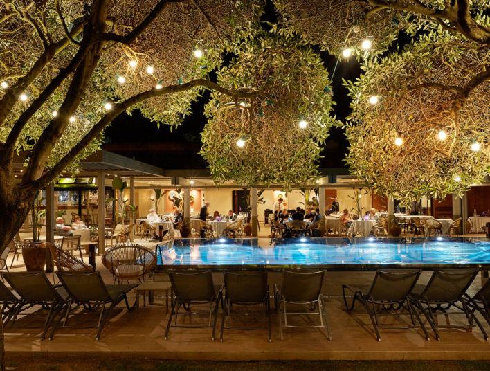 Photo de la piscine prise de nuit, on y voit autour des personnes se restaurées sur les tables qui sont en extérieures. Il y a des guirlande de lumières accrochées sur les arbres