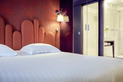 Photo du lit pris de très près avec une tête de lit orange et sa petit lampes accroché en haut à droite