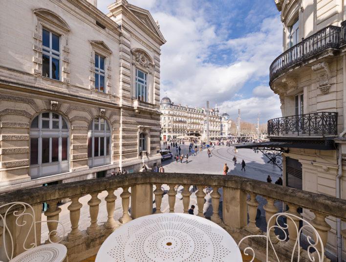 Terrasse où se trouve une table et des chaises blanches et la vue donne sur la place