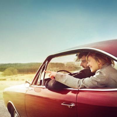 Jeune couple dans une voiture de modèle ancien avec homme au volant, à la campagne, en train de regarder un point précis dans le paysage.