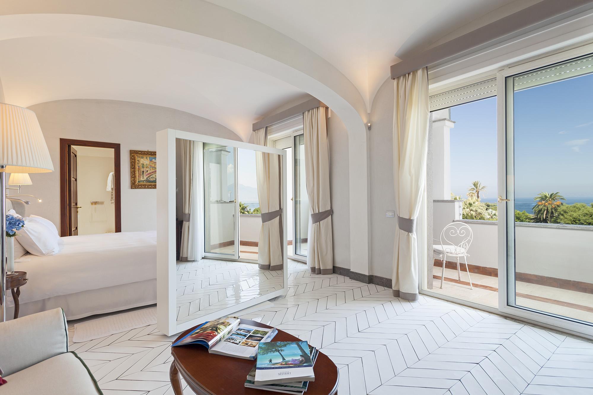 Chambre spacieuse, lumineuse et épurée avec un grand miroir près du lit double et une petite table basse en bois ainsi qu'un petit aperçu du canapé. La chambre a une terrasse qui donne une vue sur la mer.