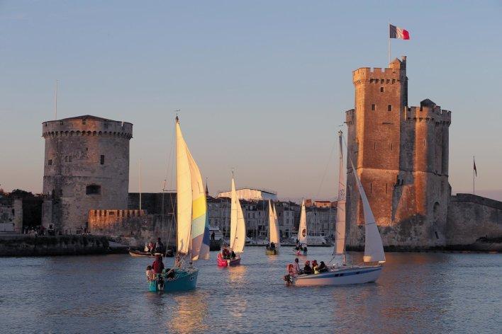 Bateaux à voile arrivant dans un port dont l'entrée se fait entre deux tours de garde en pierre, au moment du coucher du soleil