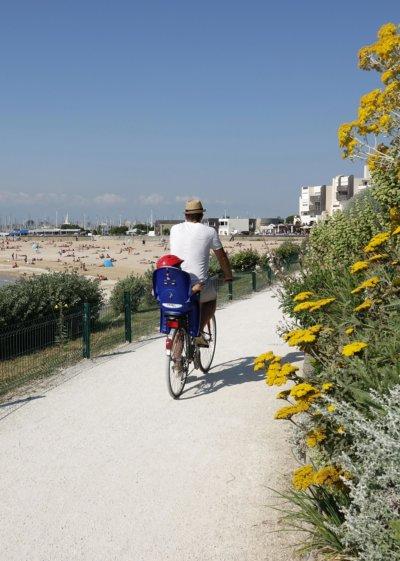 Sur un sentier en bord de plage, un homme sur un vélo avec un siège à l'arrière pour un enfant