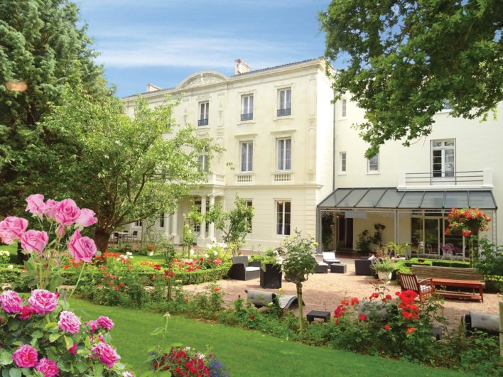 Façade d'un hôtel avec jardin à la française