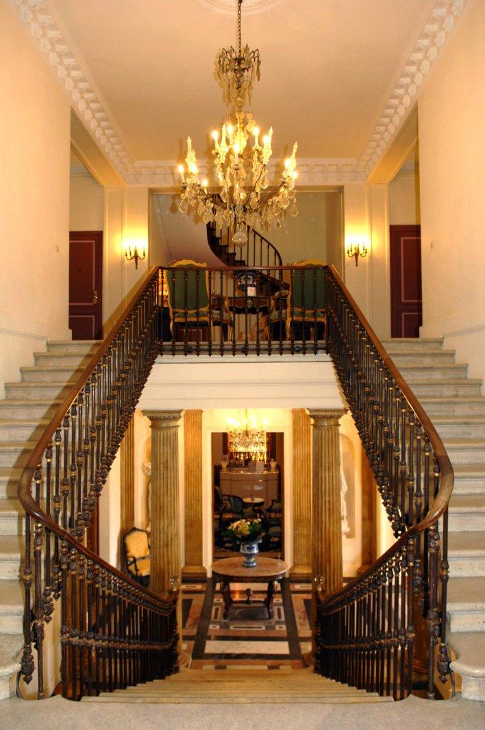 Escalier principal divisé en deux rejoignant un même palier, lustres à pampilles