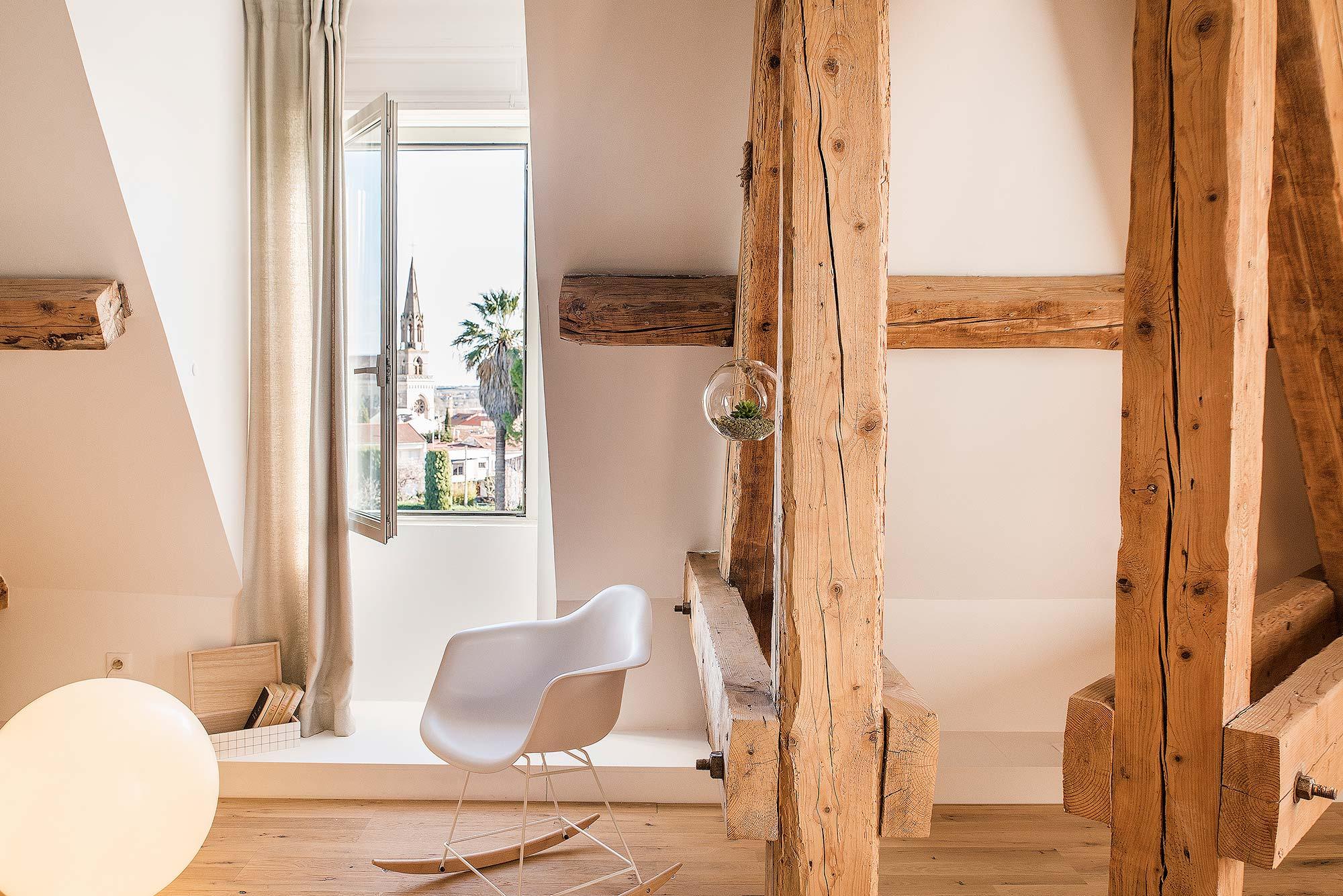 Chambre décorée avec poutres apparentes et rocking chair