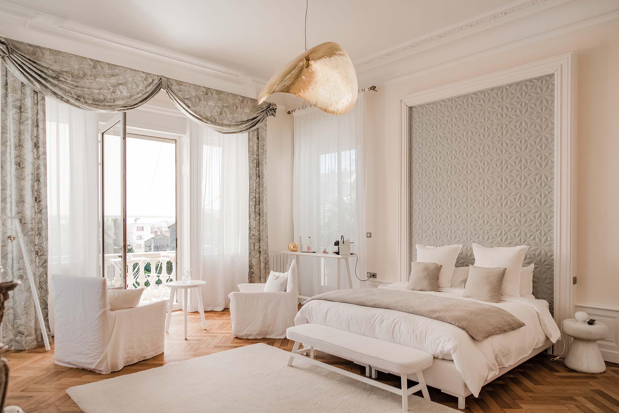 Grande chambre avec belle hauteur sous plafond, décoration dans les teintes de beige et de grisé, suspension et décoration design