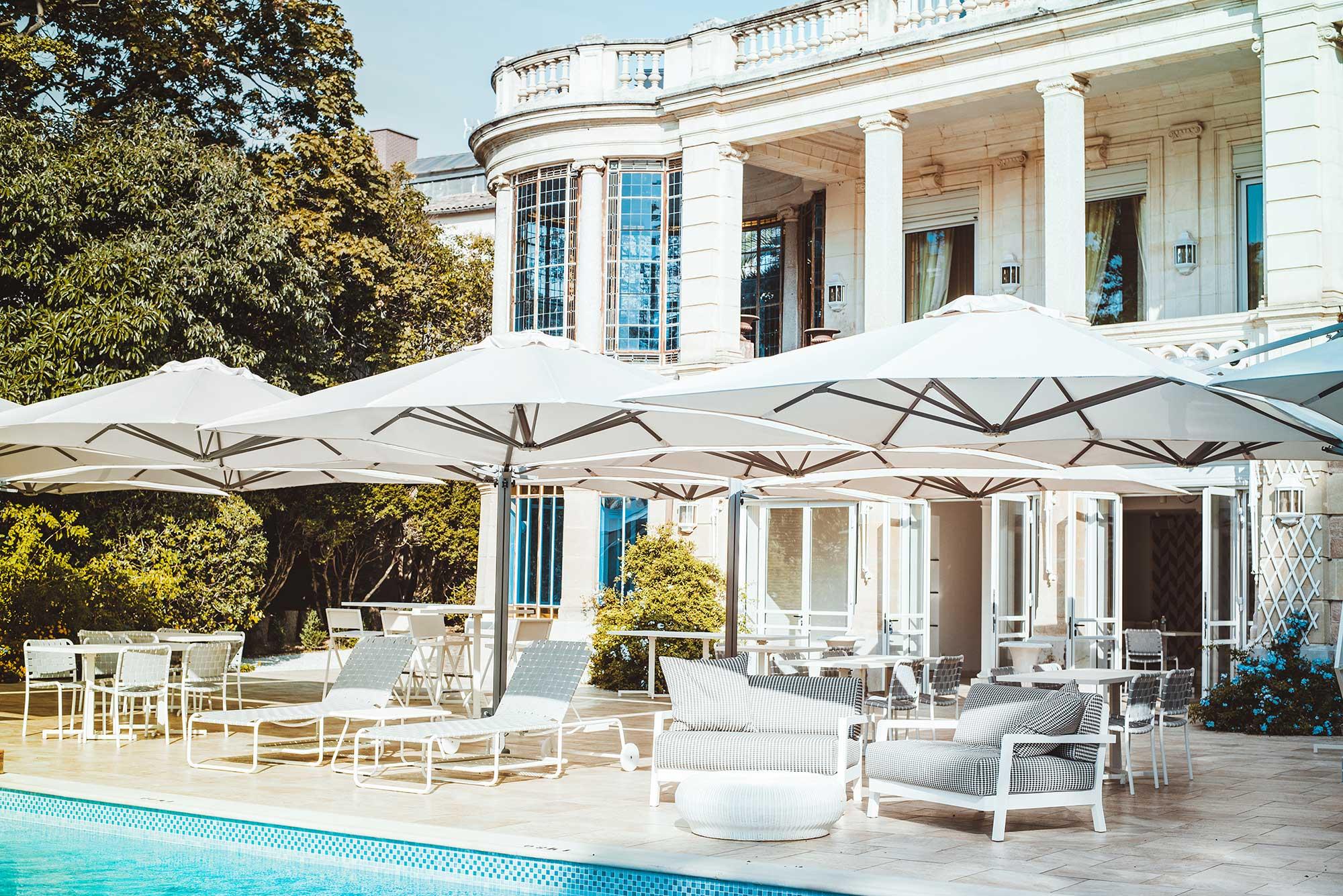 Terrasse aménagée en bordure de piscine et villa en arrière plan avec colonne romaine