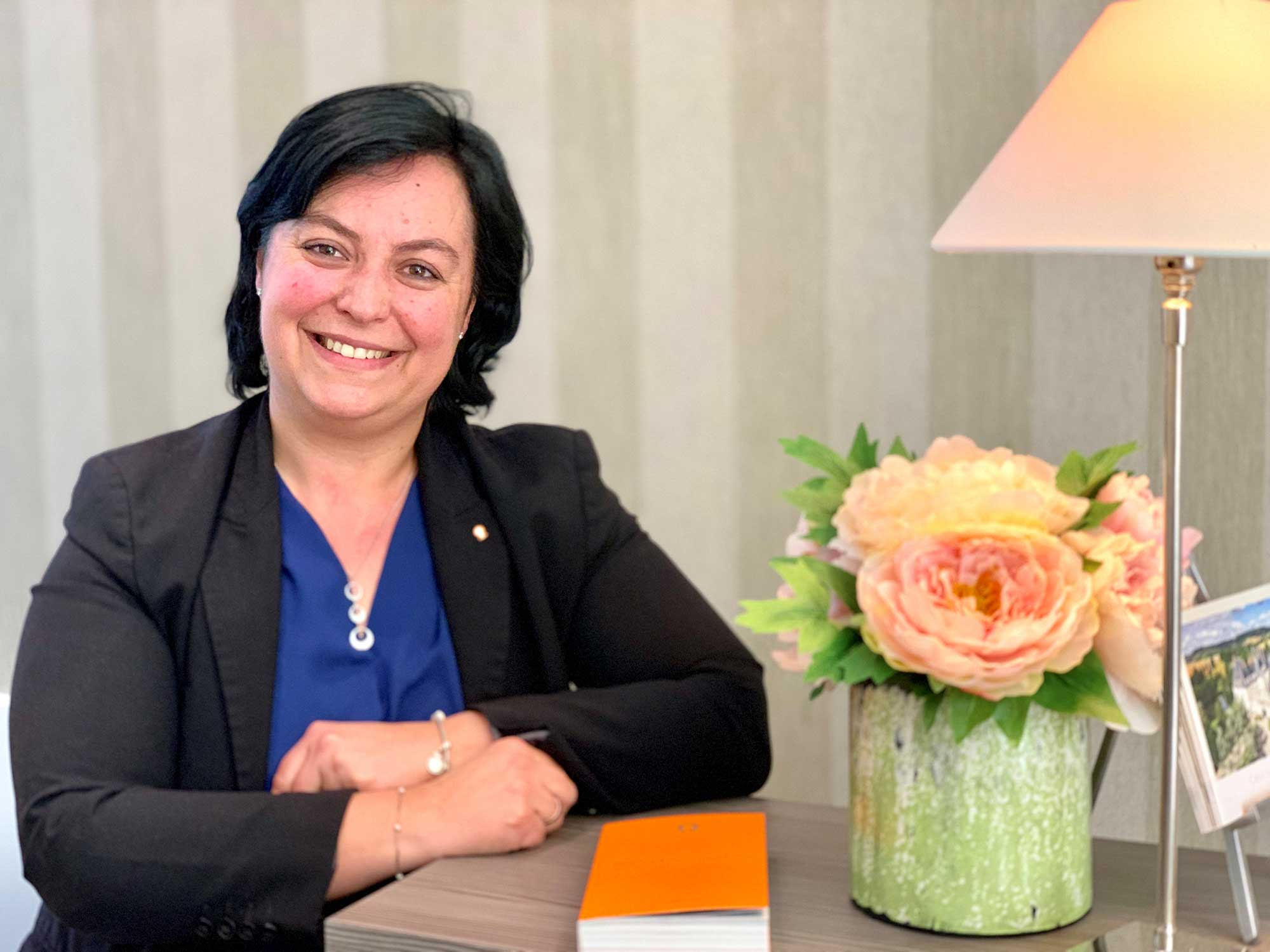 Femme accoudée à un bureau, blazer noir et chemisier bleu, un livre orange posé sur le bureau