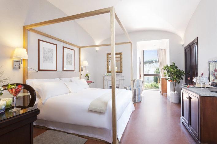 Chambre lumineuse avec lit double où se trouve deux petites lampes accroché de chaque coté du lit.