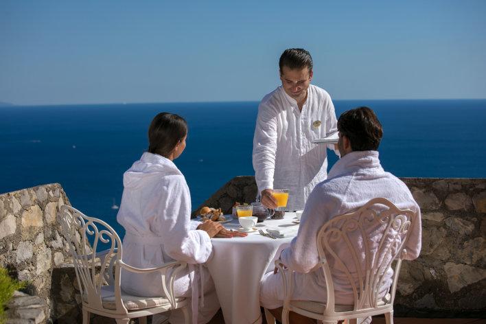 Couple pris en photo de dos en peignoir, assis devant une table pour prendre leur petit-déjeuner , un serveur se trouve en face d'eux pour les servir