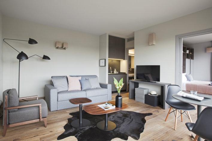 Photo de la suite double où l'on voit un salon avec une décoration design avec un canapé gris et des oreillers gris et rose, une petite table basse en bois et un meuble TV sur le coter. On aperçoit la cuisine et le lit.