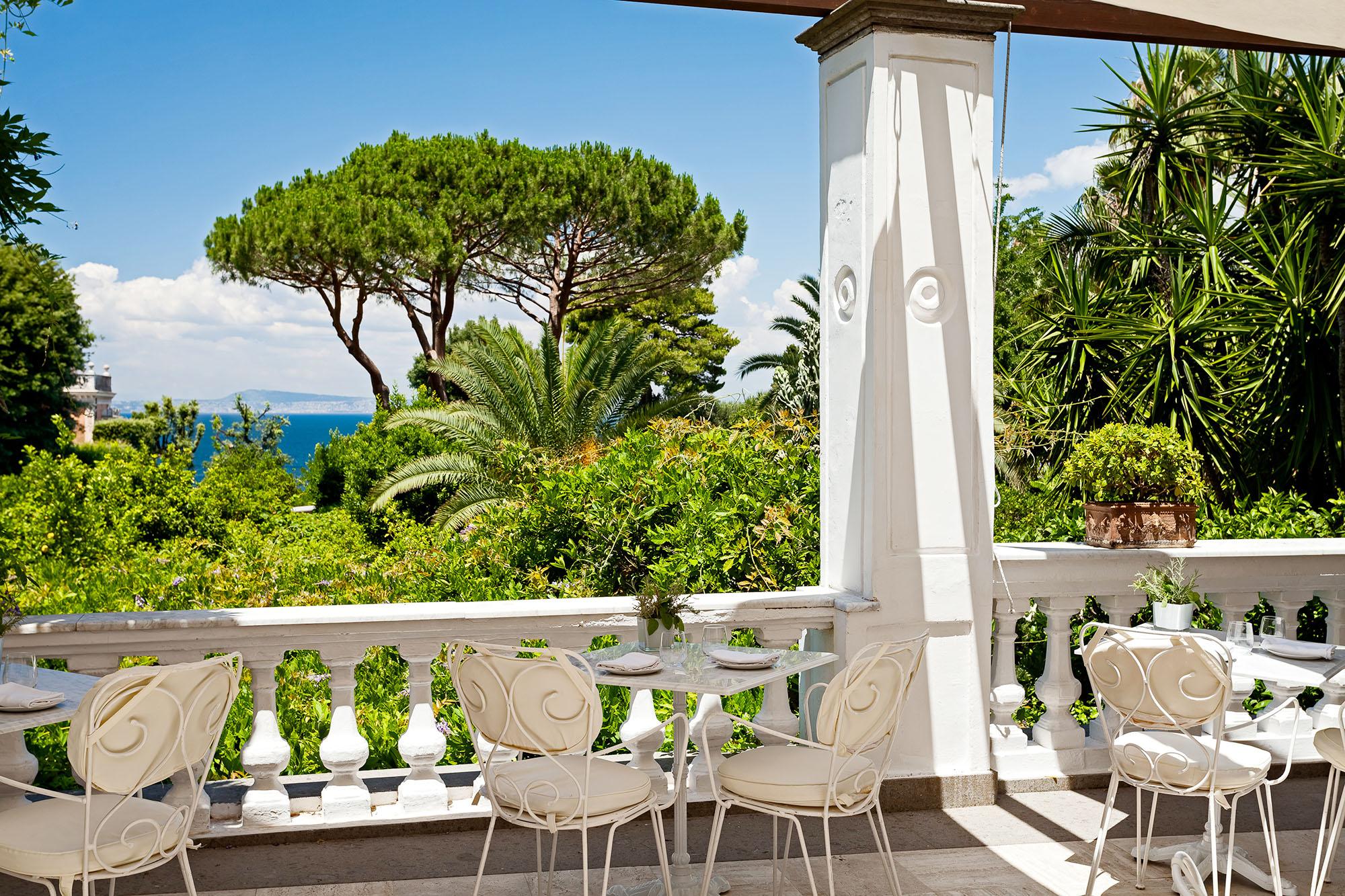 Photo de la belle terrasse avec une magnifique vue sur l'extérieur, on y trouve sur cette photo une trois table, dont une table au milieu avec deux chaises
