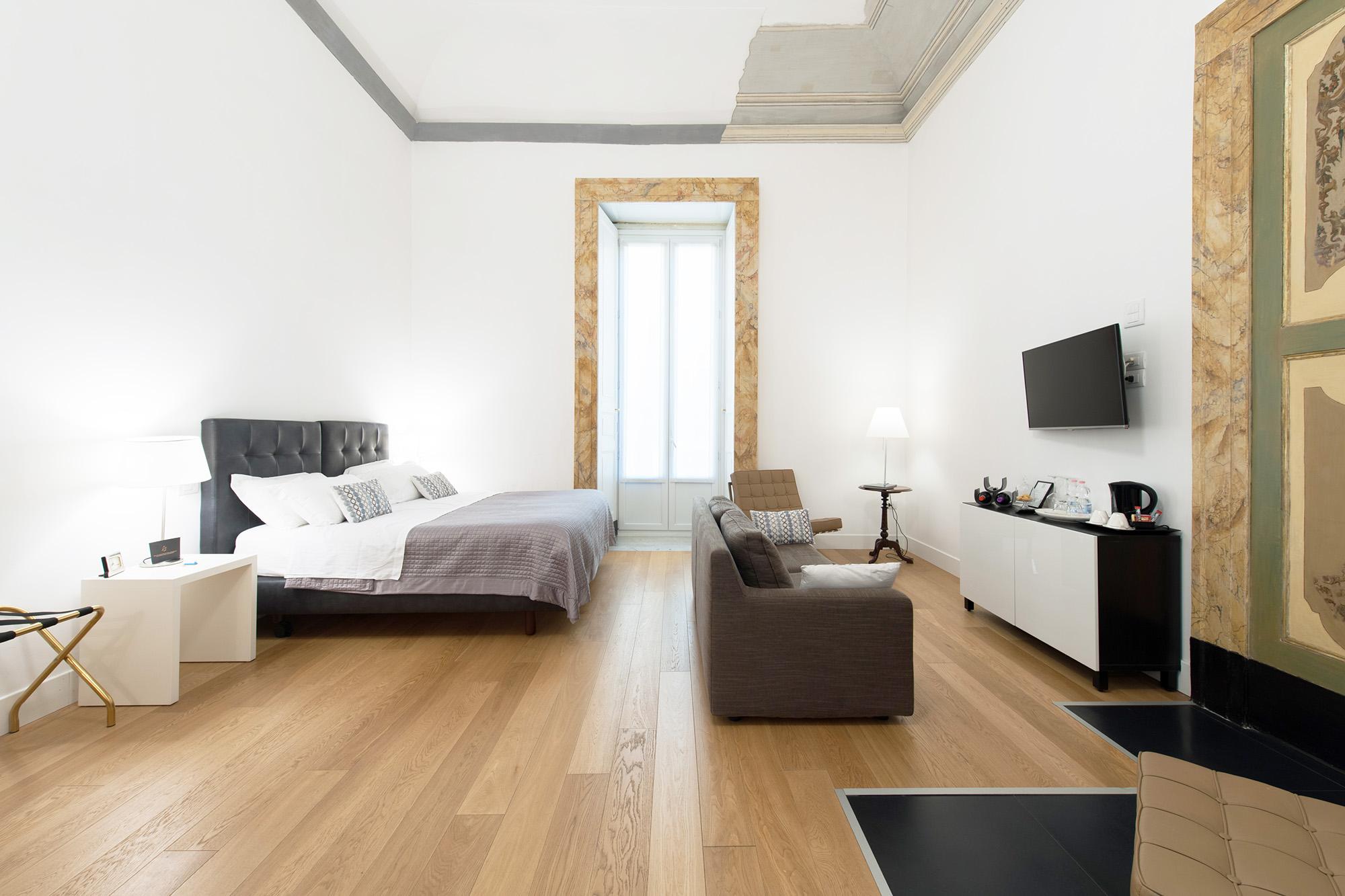 Suite double spacieuse et lumineuse avec un lit double. On y trouve un canapé devant le lit à quelques centimètres avec une télévision