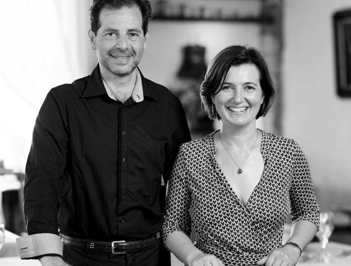 Plan américain d'un couple, un homme à gauche en chemise noir et une femme à droite en robe à motif géométrique