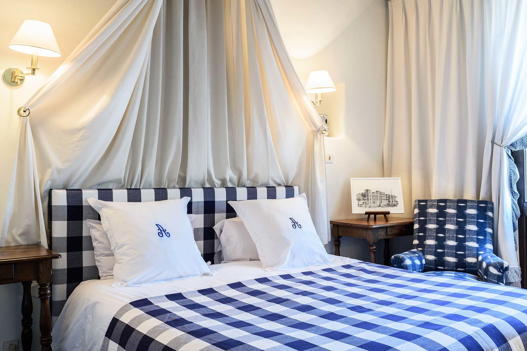 Chambre lit double avec linge à carreaux bleus et blancs