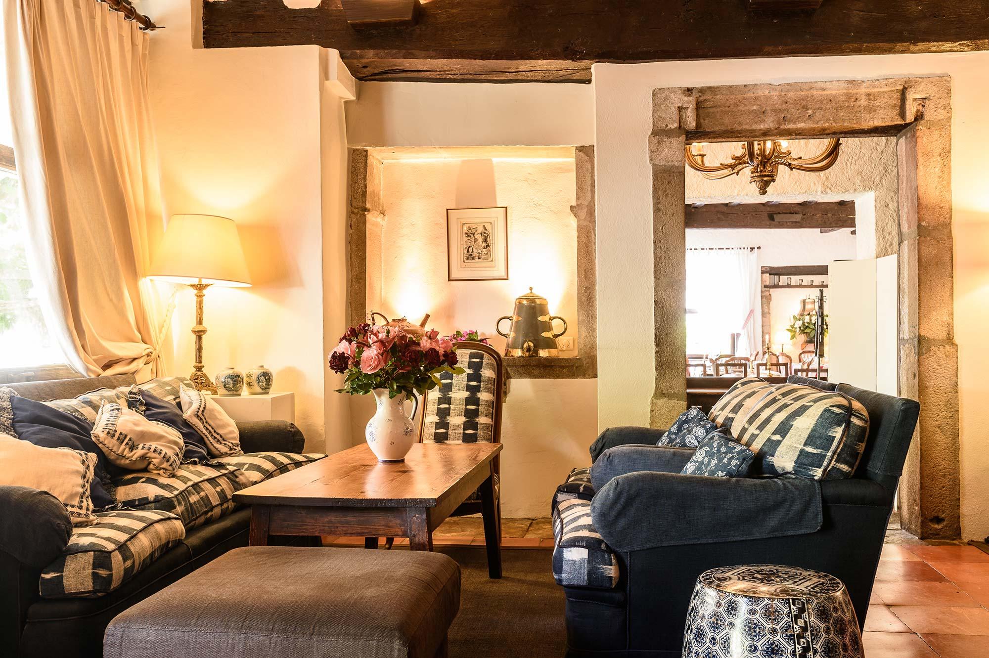 Salon avec deux canapé et une chaise, boiseries, dalle en terre cuites et linges de maison typique basque