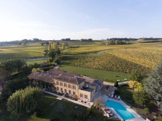 Vue aérienne d'une bâtisse typique du bordelais, avec vignes, coteaux et piscine extérieure
