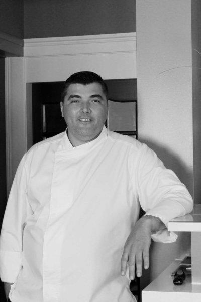Plan américain noir et blanc d'un chef en veste de cuisine blanche, accoudée à un bar