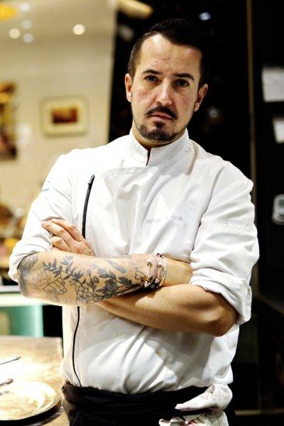 Portrait d'un chef en veste de cuisine blanche, quelques tatouages sur les bras,dans sa cuisine