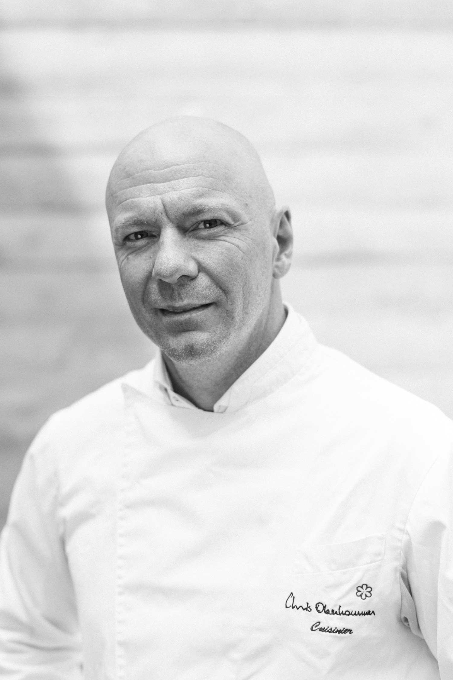 Portrait noir et blanc d'un chef en veste de cuisine blanche