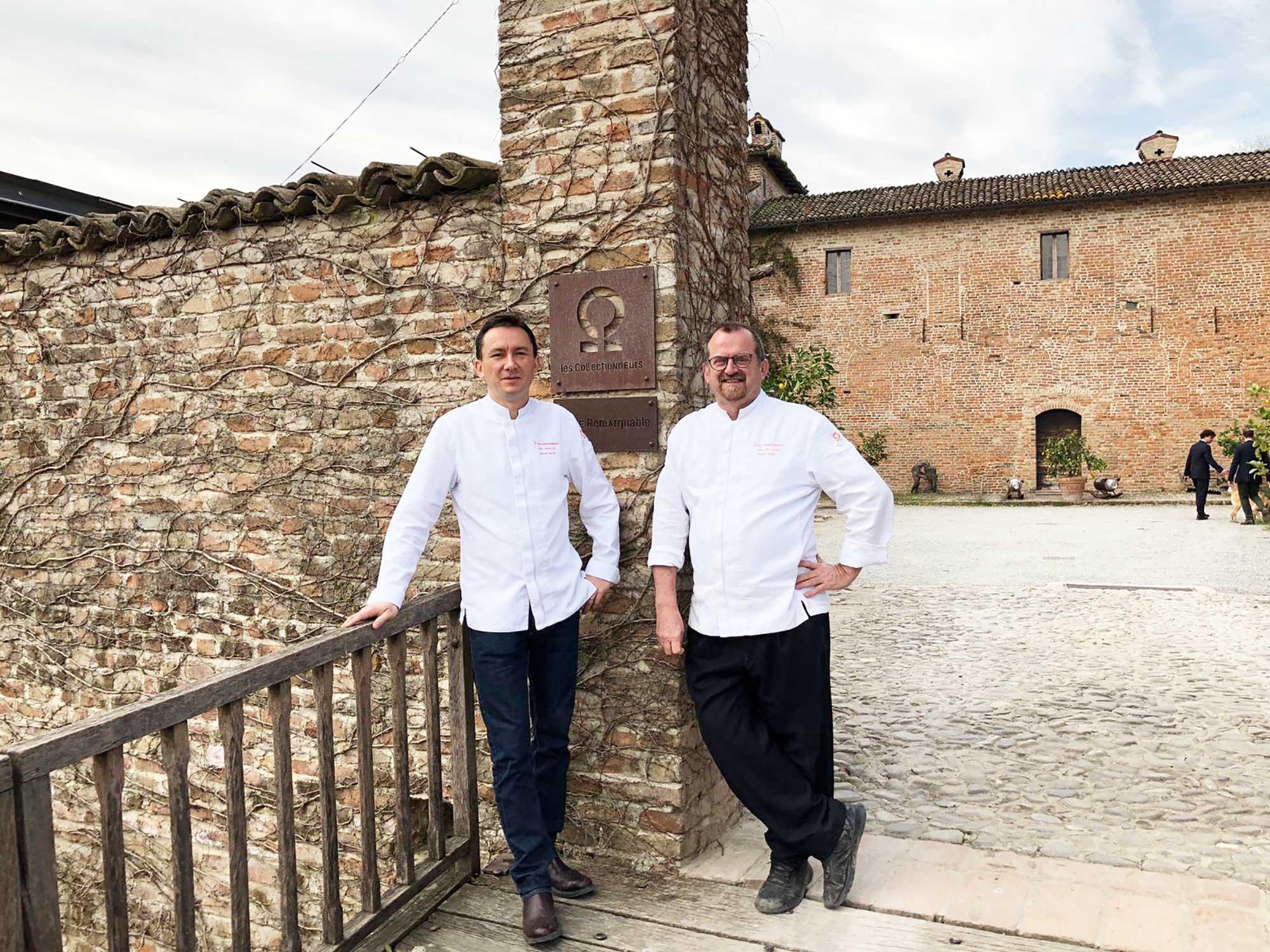 Photo d'un duo de chefs en veste de cuisine blanche à l'entrée d'un domaine